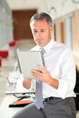 Office worker looking at internet on electronic pad — Stock Photo