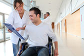 Beuatiful nurse standing by man in wheelchair — Stock Photo