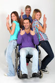 Young man in wheelchair with group of girl friends — Stock Photo