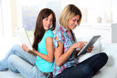 Girlfriends reading book on electronic pad — Stock Photo