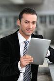 Säljare stading oustide med elektroniska tablett — Stockfoto