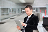 Salesman stading oustide with electronic tablet — Stock Photo