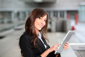 Businesswoman standing outside with electronic tablet — Stock Photo