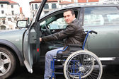 Young man in wheelchair getting in his car — Stock Photo