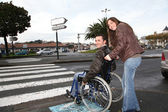 Woman helping friend in wheelchair cross the street — Stock Photo