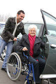 Giovane uomo assistere senior donna in sedia a rotelle — Foto Stock