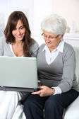Elderly woman with grandaughter with laptop computer — Stock Photo