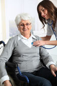 Elderly woman in wheelchair with nurse at home — Stock Photo