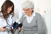 Closeup of nurse checking senior woman blood pressure — Stock Photo