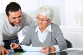 Young man helping elderly woman with paperwork — Stock Photo