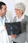 Doctor showing x-ray results to elderly woman — Stock Photo