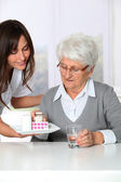 Nurse bringing medicine to elderly woman — Stock Photo