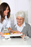 Beautiful nurse bringing meal tray to old woman at nursing home — Foto de Stock