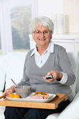 Elderly woman sitting in sofa with lunch tray — Stock Photo