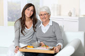 Elderly woman and home carer sitting in sofa with lunch tray — Stok fotoğraf