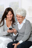 Young woman showing how to use mobile phone to grandmother — Stock Photo