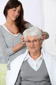 Genç kadın yaşlı kadın bir saç kesimi yapıyor — Stok fotoğraf
