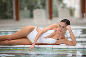 Beautiful woman laying by a thalassotherapy pool — Stock Photo