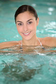 Beautiful young woman relaxing in seawater pool — Stock Photo