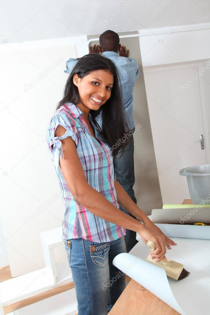 Couple putting new wallpaper in room — Stock Photo #18222225