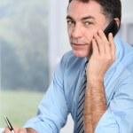 Businessman on the phone writing on agenda — Stock Photo #18249567
