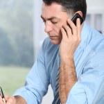 Businessman on the phone writing on agenda — Stock Photo #18249569