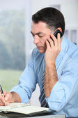Businessman on the phone writing on agenda — Stock Photo
