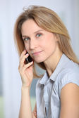 Closeup of beautiful office worker talking on the phone — Stock Photo
