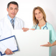 Medical team showing white board — Stock Photo #18250283