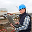 Engineer on construction site with laptop computer — 图库照片