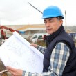 Engineer on construction site with building plan — Foto de Stock   #18250733