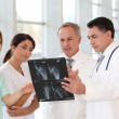 Group of doctors and nurses looking at xray — Stock Photo