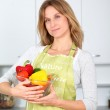 Woman in kitchen ready to prepare meal with vegetables — Stock Photo