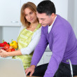 Stock Photo: Couple in kitchen looking for cooking receipe