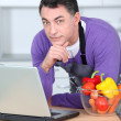 Man in kitchen with laptop computer — Stock Photo