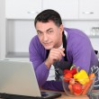 Man in kitchen with laptop computer — Stock Photo #18252233