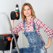 Woman using electric drill at home - Stock Photo