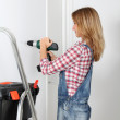 Woman using electric drill at home — Stock Photo #18252283