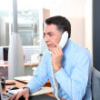 Businessman in the office talking on the phone — Stock Photo
