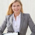 Beautiful blond businesswoman standing outside — Stock Photo
