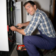 Plumber fixing heater - Stockfoto