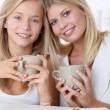 Blond woman and blond girl having breakfast - Stock Photo