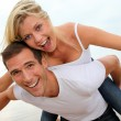 Happy couple enjoying vacation on a sandy beach - Stock Photo