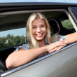Young woman driving new car - Stock Photo