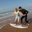 Man teaching young woman to surf — Stock Photo #18256613