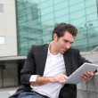 Man using electronic tablet in front of modern building — Stock Photo #18257915