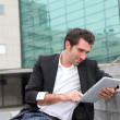 Stock Photo: Man using electronic tablet in front of modern building
