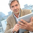 Stock Photo: Handsome guy in town using electronic tablet