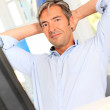 Man relaxing in office with stretched arms — Stock Photo #18258299