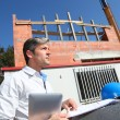 Entrepreneur checking plan on construction site — Stock Photo